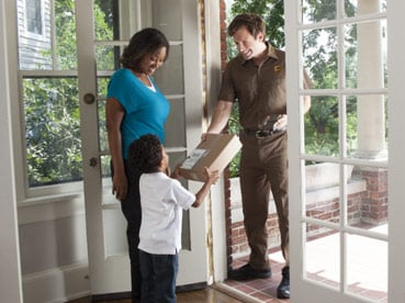 Woman and child receiving package from UPS driver