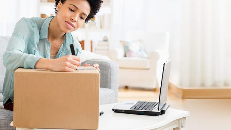 Woman writing on package