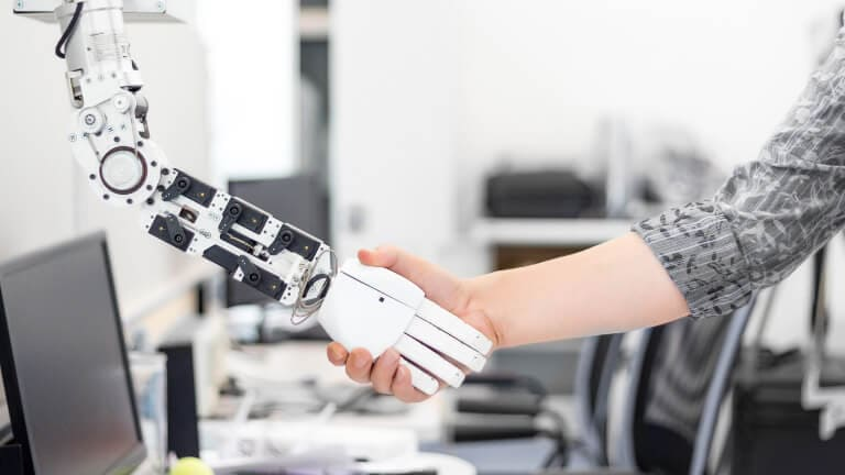 A woman shaking a robots hand
